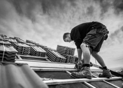 Portrait en action d'un artisan couvreur qui découpe des voliges sur un toit. Une photo originale en noir et blanc, le ciel est chargé.