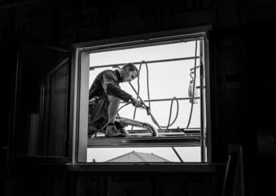 Zingueur en train de souder un chêneau. La photo de l'artisan est en noir et blanc, l'image originale montre la scene a travers une fenêtre cerclée d'un fond noir